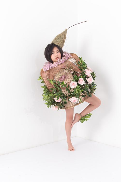Lồng chim xinh xắn được trang trí hoa hồng và cây lá để giúp tạo hình của Khánh An thêm phần cuốn hút.