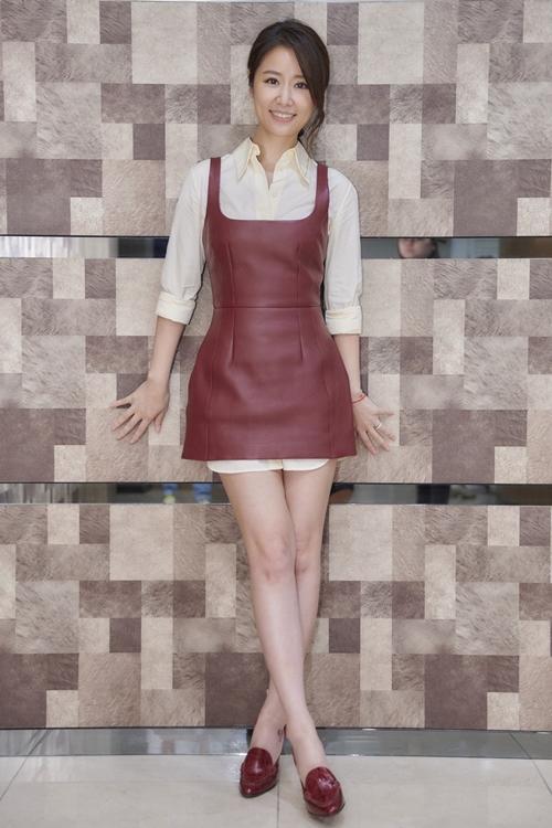 Lâm Tâm Như diện sơ mi trắng, phối với váy da nâu và giày đồng điệu trong buổi khai máy tại một trường đại học ở Đài Bắc.