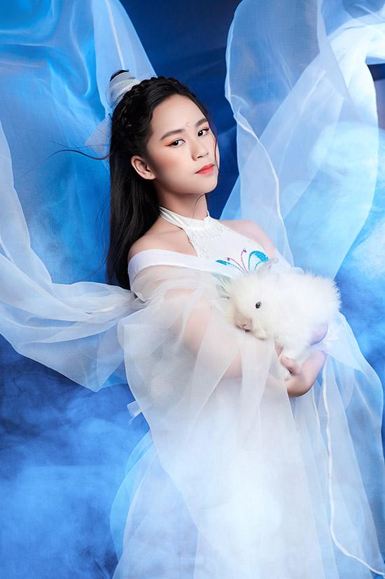 Bella Vũ trong thiết kế váy cổ yếm kết hợp áo choàng voan thướt tha của Phương Hồ tạo dáng cùng bạn diễn đặc biệt. Mẫu nhí yêu động vật và rất thích loài thỏ trắng.