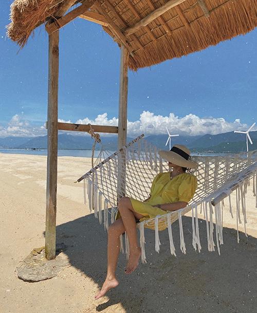 Đầm cổ điển dáng suông nhẹ nhàng mang lại cảm giác thoải mái được Tăng Thanh Hà mix cùng mũ nan khi đi du lịch biển.