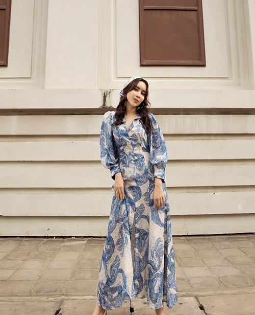 Váy in hoạ tiết với phần tay bồng nhẹ nhàng, xẻ chân váy chừng mực giúp Lưu Hương Giang duyên dáng hơn khi xuống phố.