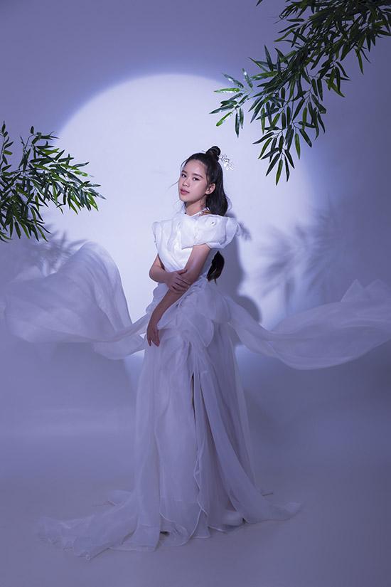 Hoa hậu nhí lộng lẫy với thiết kế Nàng trăng của Nguyễn Minh Tuấn. Bộ váy được thực hiện theo kỹ thuật tạo khối 3D để mô phỏng hình ảnh những áng mây trắng bao quanh chị Hằng. Bella Vũ thích chất liệu voan mỏng nhẹ, bồng bềnh tạo cảm giác thoải mái cho người mặc.