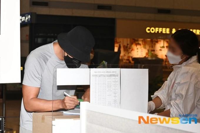 Hyun Bin khai báo y tế và kiểm tra sức khỏe theo hướng dẫn của nhân viên sân bay.