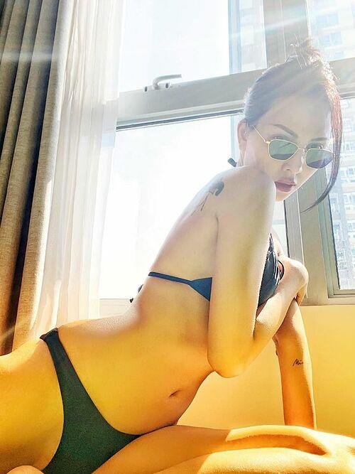 Người mẫu Minh Triệu tắm nắng kết hợp ép dẻo ngay tại nhà. Cô chia sẻ: Hình như hơi ít ở nhà nên bây giờ mới biết góc này có nắng. Lết ra liền vừa tắm nắng vừa ép dẻo, không kịp make up chỉ kịp tô son.