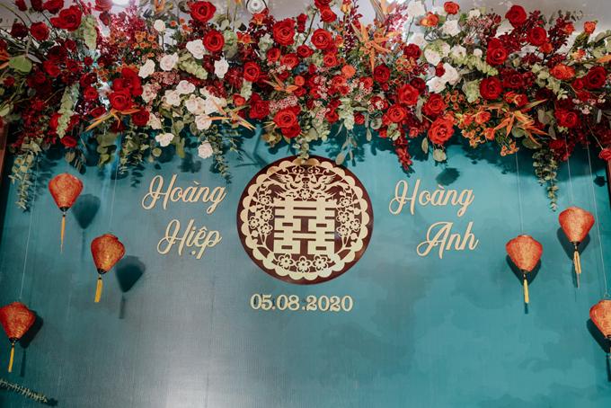 Loài hoa chủ đạo để tô điểm cho không gian là những đóa hồng nhung, hồng phấn xen kẽ các dây lá li ti, hoa thiên điểu. Các loài hoa trang trí cho buổi lễ đều là hoa tươi nhập khẩu, có màu sắc đẹp và hương thơm đặc trưng. Phông nền của khu vực chính giữa phòng khách mang nét độc đáo của các chi tiết truyền thống. Họa tiết chữ hỷ mang sắc đỏ đun và vàng kim. Đèn lồng đỏ trở thành điểm nhấn giúp làm nổi nét truyền thống ở không gian.