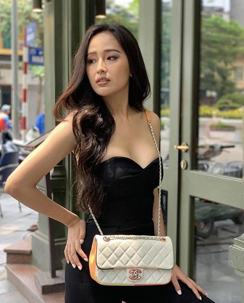Mai Phương Thuý khoe vai thon và vòng một gợi cảm với jumsuit tông đen. Hoa hậu chọn túi Chanel tông màu tương phản để mix đồ dạo phố.