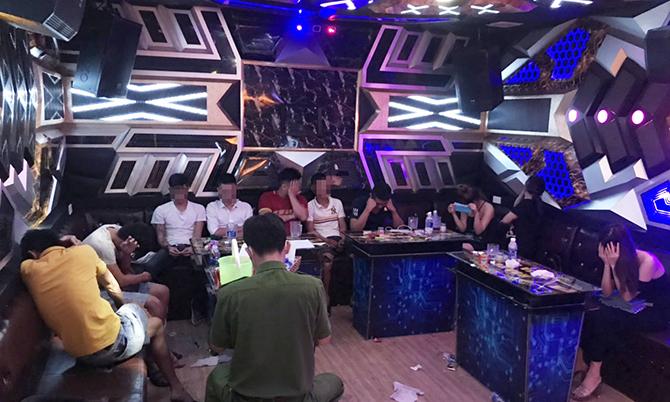 Công an lập biên bản xử lý 10 người sử dụng ma túy trong phòng hát karaoke. Ảnh: Đại Hiệp.
