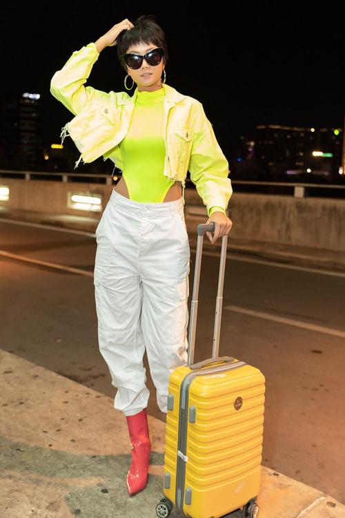 Mẫu monokini tông màu nenon được HHen Niê mix cùng quần lưng cao, áo jacket tiệp màu, bốt da bóng để thể hiện nét phá cách khi ra sân bay.