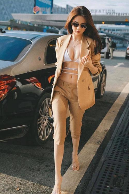Trên bộ suit nâu nhạt hợp xu hướng thu đông, Ngọc Trinh chọn áo biki dây đan để tạo điểm nhấn cho set đồ khi chuẩn bị làm thủ tục xuất cảnh.