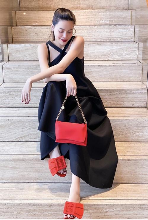 Đầm suông dáng dài, trang trí dây đan chéo điệu đà được Hồ Ngọc Hà phối cùng bộ phụ kiện tông đỏ nổi bật.