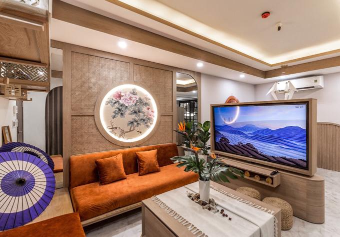 Phòng khách có bộ ghế sofa mềm mại với tông màu cam đất giúp làm nổi không gian. Hệ TV ngăn giữa phòng khách và khu ăn có thể xoay được. Dù cho gia chủ ngồi ở khu vực nào cũng có thể xem TV một cách dễ dàng, thuận tiện.