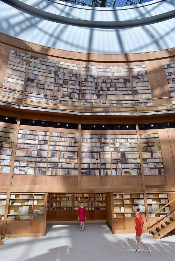 Sân khấu hoành tráng này chính là cách tưởng nhớ tinh tế của nữ giám đốc sáng tạo 57 tuổi dành cho hai linh hồn của thương hiệu: Coco Chanel và Karl Lagerfeld. Virginie Viard mô phỏng thư viện giả tưởng cho Coco với những khối đá chặn sách hình sư tử - cung hoàng đạo của người sáng lập Chanel, và những chiếc đèn nghệ thuật gợi nhớ thời thanh xuân của bà. Bên cạnh đó, chưa đầy hai tuần trước, cũng tại bảo tàng Grand Palais, chương trình tưởng niệm Karl Lagerfeld diễn ra với hàng trăm màn hình lớn được lắp đặt để chiếu những thước phim quay trong thư viện cá nhân của ông, khẳng định sự liên quan rõ ràng đến ý tưởng sàn diễn do Virginie Viard thực hiện.