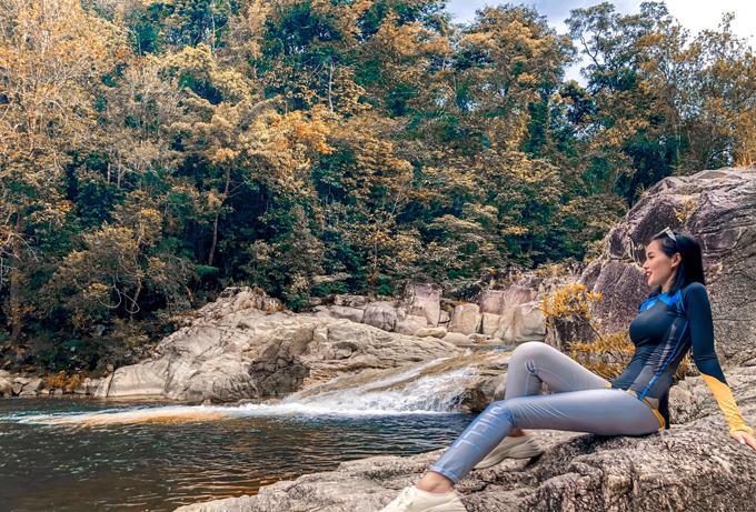 Hotgirl Hà Nội một thời ngồi nghỉ bên dòng suối giữa rừng nhiệt đới. Du khách có thể xuống tắm hoặc ngồi thư giãn giữa không gian trong lành. Hòn Bà cao hơn 1.500m, cảnh vật trên đỉnh núi thơ mộng, mây nước bồng bềnh, suối trong vắt chảy róc rách, được ví như chốn bồng lai tiên cảnh. Tâm Tít diện đồ thể thao bó sát, co giãn tiện dụng, phù hợp cho những hoạt động thể chất.