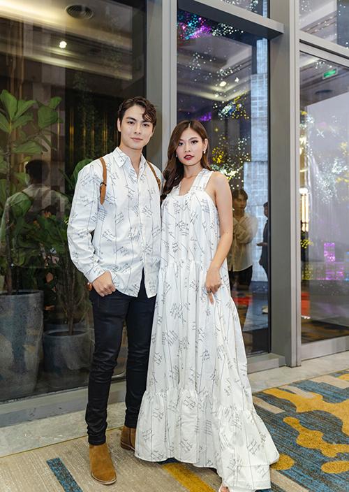 Đôi vợ chồng trẻ cùng diện trang phục ton-sur-ton với thiết kế sơ mi và váy không kén dáng có cùng chất liệu, hoạ tiết.