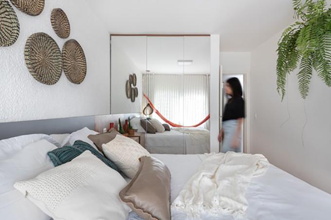 Không gian phòng tắm được cắt giảm để tăng diện tích cho tủ quần áo, tường gương phản chiếu cảnh quan bên ngoài của phòng ngủ.