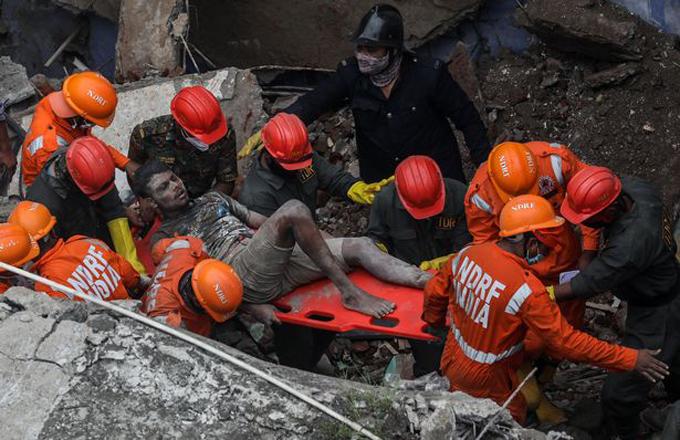 Một người đàn ông được giải cứu khỏi hiện trường sập tòa nhà 3 tầng ngoại ô Mumbai. Ảnh: Rex.