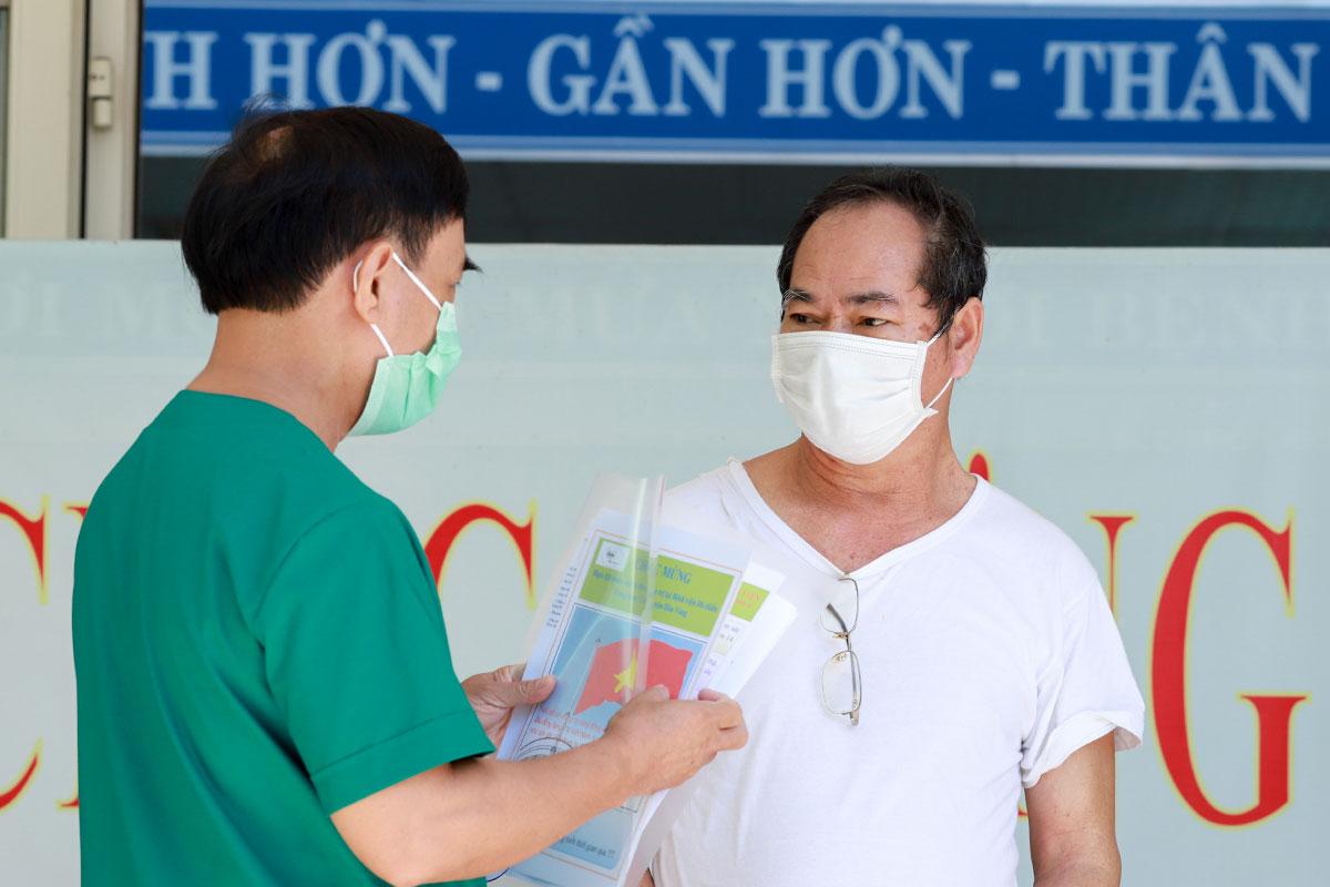 Lãnh đạo Bệnh viện Dã chiến Hoà Vang trao giấy xuất viện, dặn dò bệnh nhân 936 tiếp tục cách ly tại nhà 14 ngày. Ảnh: Ngọc Trường.