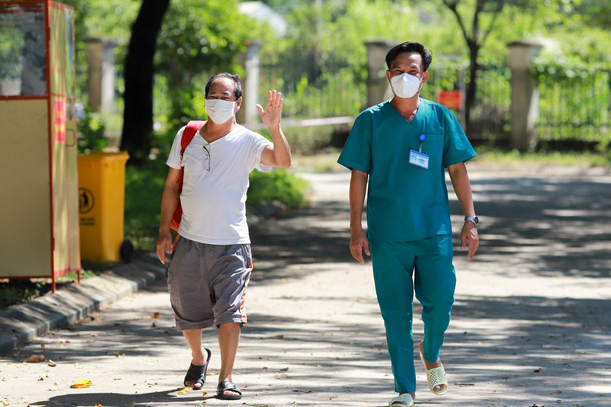 Bệnh nhân 936 vẫy tay chào các y, bác sĩ khi được xuất viện. Ảnh: Ngọc Trường.