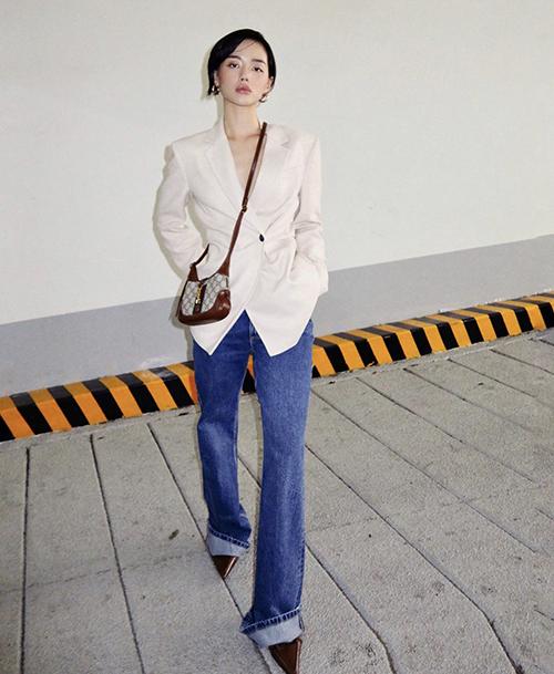 Khi không diện các kiểu váy hot trend điệu đà, Khánh Linh vẫn tạo nên sức hút nhờ lối mix-match thuyết phục với vest trắng, jeans xanh cổ điển và túi đeo chéo Gucci mới ra lò.