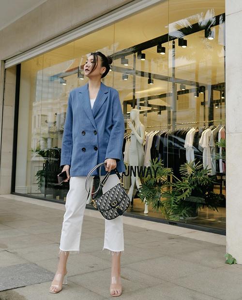 Khi diện áo vest dáng rộng trên tông xanh hợp trend 2020, Thanh Hằng chọn nguyên set đồ trắng đến mix đồ. Túi Dior sang chảnh được siêu mẫu chọn lựa để tăng sức hút cho trang phục dạo phố.