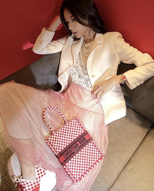 Phí Phương Anh phá bỏ mặc định diện vest dễ khiến phái đẹp già hơn tuổi nhờ cách mix áo khoác trắng cùng áo thun ký tự, chân váy xoè chấm bi xinh xắn.