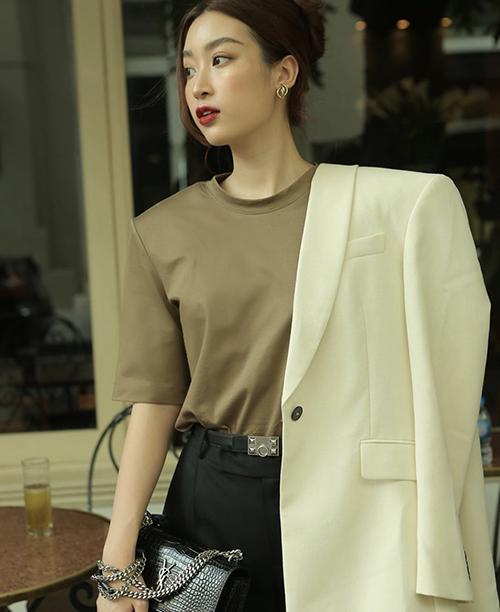 Đỗ Mỹ Linh đổi gió cho phong cách street style với set đồ mang hơi hướng menswear. Áo blazẻ màu trắng kem được mix-match nhịp nhàng cùng áo thun vai thô, quần âu tông đen.