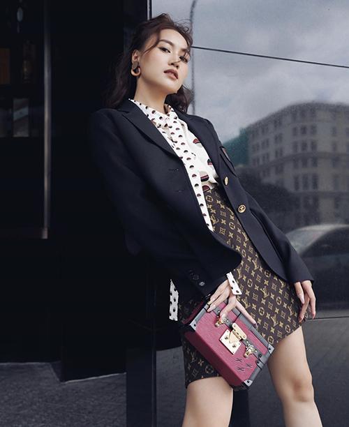 Áo vest đơn sắc được Lan Ngọc gia cố cho set đồ dạo phố mùa thu gồm áo thắt nơ hoạ tiết chấm bi, chân váy nâu trang trí logo Louis Vuitton và clutch xinh xắn.