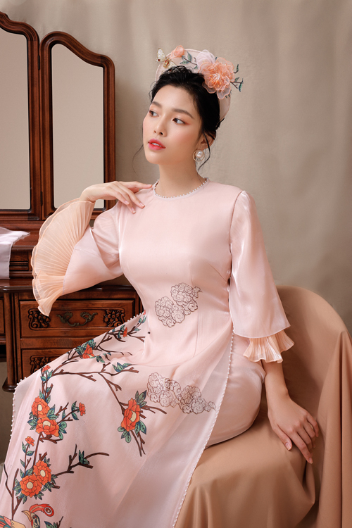 Tay áo voan kết hợp phần vải nhún tạo nên sự cuốn hút trong từng cái nhấc tay của cô dâu. Vạt áo được đính hạt, họa tiết hoa cỏ bung nở rực rỡ tạo thành điểm nhấn thị giác của áo dài.