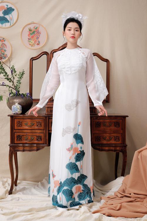 Một gợi ý khác cho tân nương là áo dài trắng cũng có họa tiết đầm sen khi sánh bước bên tân lang. Tấm áo có tay dài cách điệu với họa tiết ren, có thêm họa tiết chữ hỷ nơi ngực.