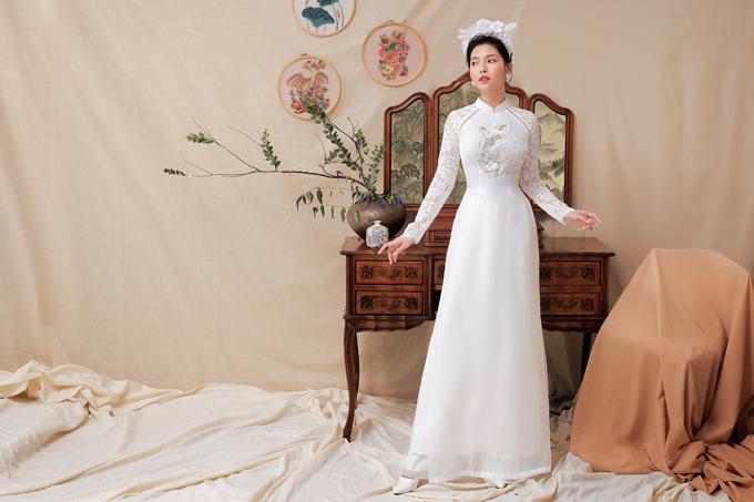 Áo nữ có tay ren, chất liệu khác biệt so với vải làm thân áo. Cô dâu có thể kết hợp thêm mấn đội đầu để hoàn thiện vẻ ngoài trong ngày trọng đại.