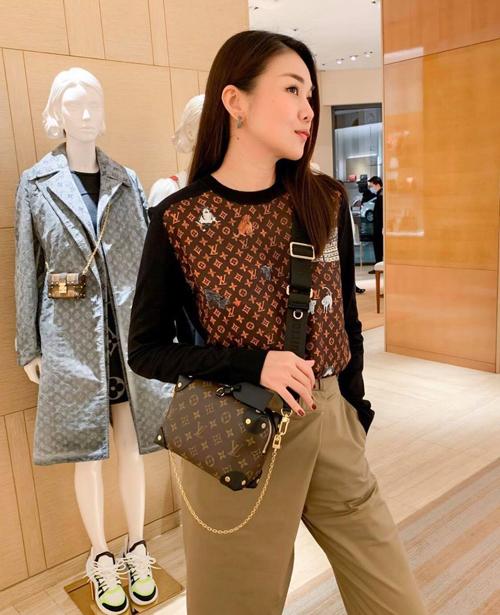 Thanh Hằng tranh thủ khoe dáng với túi mới sắm khi trú mưa ở khu thương mại nổi tiếng ở Sài Gòn.