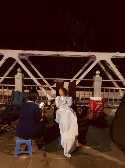Trợ lý túc trực bên cạnh trong lúc NSND Lê Khanh tranh thủ chợp mắt ở địa điểm quay ngoài trời.