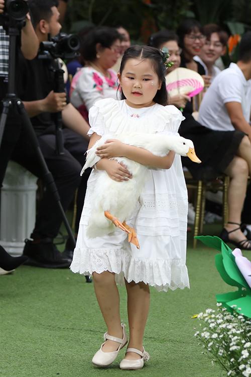Hình ảnh đáng yêu của mẫu nhí khi ôm vịt trắng để trình diễn catwalk.
