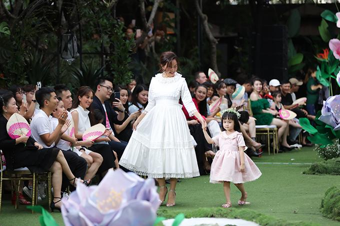 Hình ảnh bé Tuệ An diện đầm cổ điển, bước đi bẽn lẽn bên mẹ được dàn sao tham dự show diễn vô cùng thích thú.