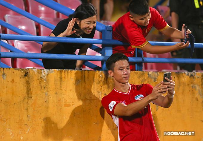 Một fan nữ lớn tuổi cũng xin chụp ảnh cùng Quế Ngọc Hải. Trung vệ xứ Nghệ vui vẻ đáp ứng đề nghị của người hâm mộ.