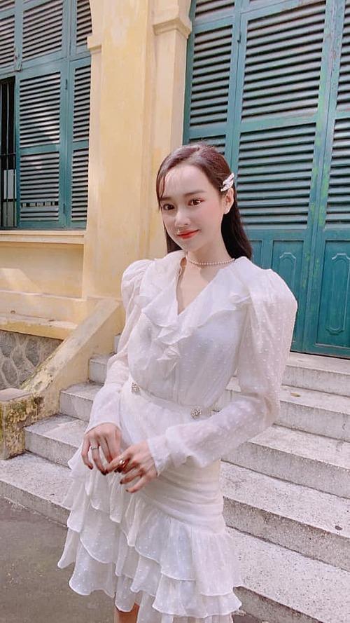Nhã Phương chuộng váy tone trắng cùng kiểu tóc suông dài giúp hack tuổi.