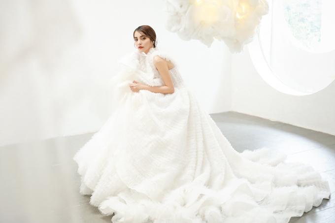 Váy cưới được lấy ý tưởng từ những áng mây trắng lững lờ trôi trên bầu trời. Để từ ý tưởng trên giấy biến thành tuyệt tác váy cưới trong hiện thực, nhóm thiết kế đã sự kết hợp giữa kỹ thuật may thủ công và đắp ren tinh xảo.