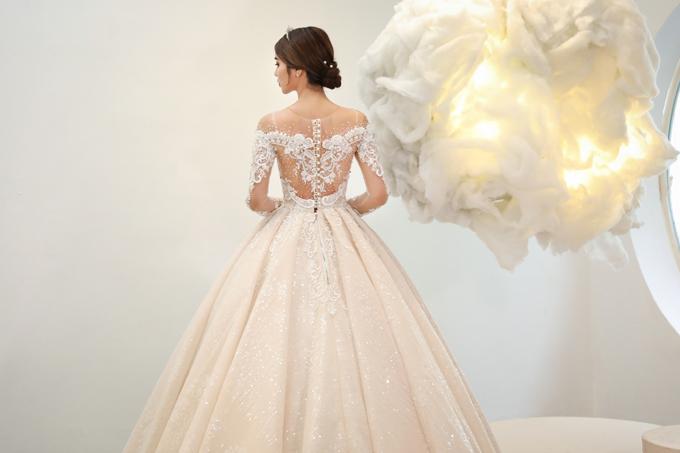 Mặt lưng váy là một bức tranh cầu kỳ từ ren nổi, giúp khách mời đắm mình với thiết kế dù ở mọi góc nhìn.