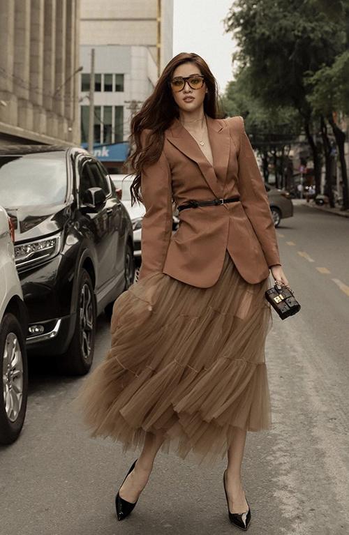 Diện áo blazer và chân váy tuyn tông màu nâu và trung tính, Khánh Vân sử dụng thêm mẫu túi mini để hoàn thiện set đồ dạo phố.