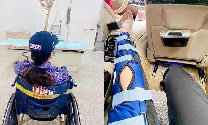 Nhật Kim Anh ngồi xe lăn sau khi chân bị rách dây chằng.