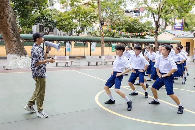 Quang Đăng cầm loa, chỉ đạo phần nhảy của Đức Phúc cùng 60 vũ công tại bối cảnh một trường THPT ở Hà Nội. Quang Đăng khen ngợi Đức Phúc nhảy đẹp và phối hợp ăn ý với dàn vũ công đông đảo.