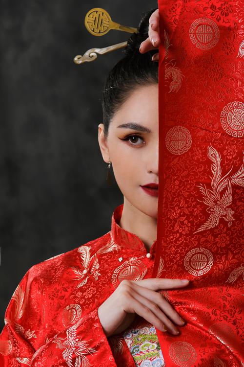 Mẫu áo đỏ may bằng vải gấm có họa tiết chim phượng hoàng chủ đạo, rất phù hợp cho những dịp trọng đại như lễ cưới, đám hỏi.