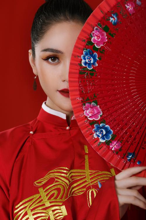 Mẫu áo lụa trơn nhưng không kém phần nổi bật bởi cách sử dụng hai màu tương phản là sắc đỏ của áo và họa tiết thêu màu vàng trước ngực.