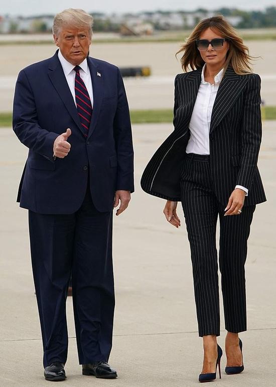 Trong khi đó bà Melania mặc bộ vest đen kẻ sọc nhỏ, áo sơmi trắng và giàu cao gót đồng màu. Tuy nhiên, trang phục Đệ nhất phu nhân không phải sản phẩm của một nhà thiết kế Mỹ mà đến từ nhà mốt Italy Dolce & Gabbana có giá hơn 3.300 USD. Bà Melania xõa tóc tự nhiên, đeo cặp kính to bản khi bước xuống Không lực Một cùng chồng. Ảnh: AFP.
