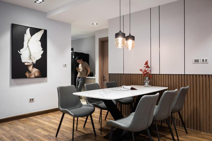 Bàn ăn mặt đá còn chân sắt được sơn đen. Ghế ăn bọc da màu xám đậm. Tất cả giúp tạo nên vẻ đẹp sang trọng, hiện đại cho căn hộ.
