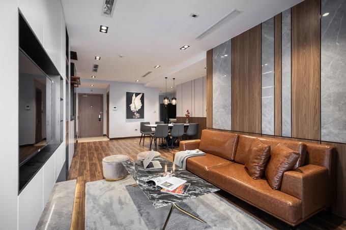Đá xám Italy được sử dụng làm vật liệu ốp tường, kệ TV kết hợp gỗ, sofa da, đôn nỉ, bàn trà đá đen đặt trên nền thảm lông ngắn màu lông chuột.