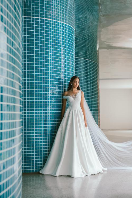 Tấm váy cưới có vai bất đối xứng, được điểm ren nơi ngực áo. NTK dùng nhiều chất liệu từ cứng cáp tới mềm mại, phom dáng từ ôm gọn tới xòe to cho trang phục cưới.
