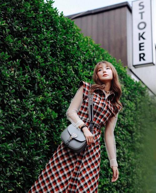Mẫu túi cháy hàng của Dior được Minh Hằng chọn làm điểm nhấn khi diện váy sơ mi, họa tiết hợp mốt để xuống phố.