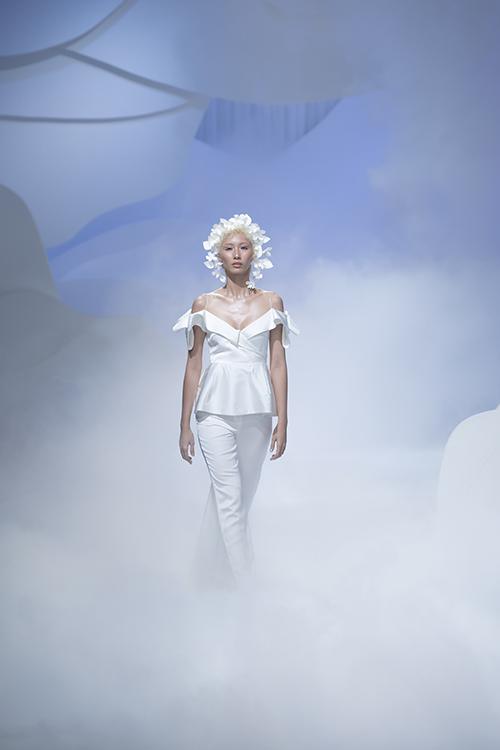 Áo hai dây đuôi dài, phần bẻ lật vai phối cùng quần trắng là một trải nghiệm sáng tạo của Trương Thanh Hải, tạo sự khác biệt trong bộ sưu tập. Phụ kiện vòng hoa là điểm nhấn trang trí cho toàn bộ bộ sưu tập. Mỗi cánh hoa được xử lý và tạo hình công phu từ vải trắng.