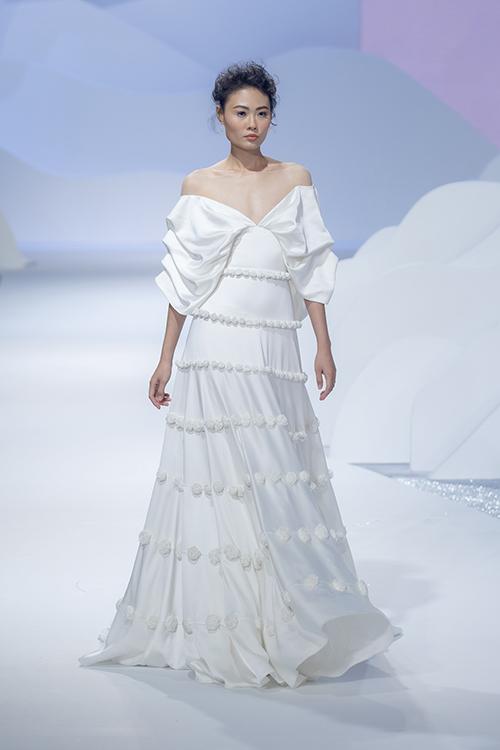 Váy chia tầng được trang trí bởi hoa văn vải. Tay áo trễ vai được xếp nếp cầu kỳ, phá cách.